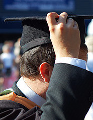 Man dressed in mortar board and graduation gown.