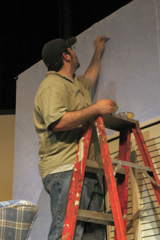 photograph of man on ladder painting wall.