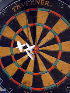 A target with three darts in the bullseye.