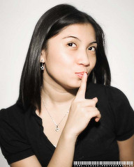 "Woman holding finger to lips as if saying, ""Shhh."""